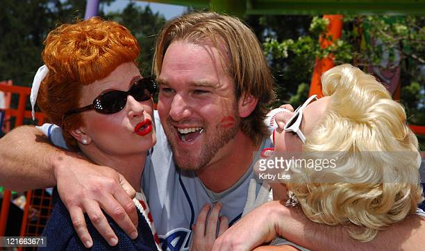 Los Angeles Dodgers pitcher Derek Lowe receives a kiss from Diane Vincent portraying Lucille Ball and Tia Marrie portraying Marilyn Monroe at a news...