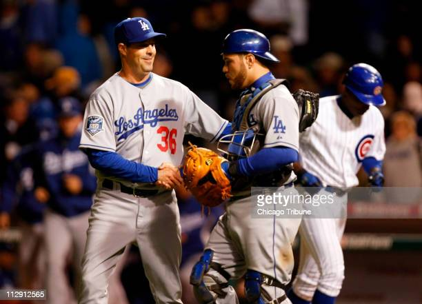Los Angeles Dodgers pitcher Greg Maddux and catcher Russell Martin celebrate a 72 victory against the Chicago Cubs in Game 1 of the National League...