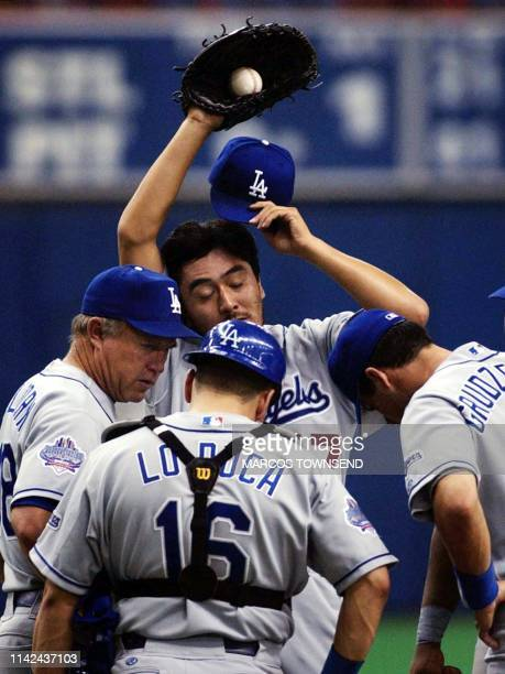 Los Angeles Dodgers' pitcher Kazuhisa Ishii of Japan wipes his brow while meeting with pitching coach Jim Colborn catcher Paul Lo Duca and second...