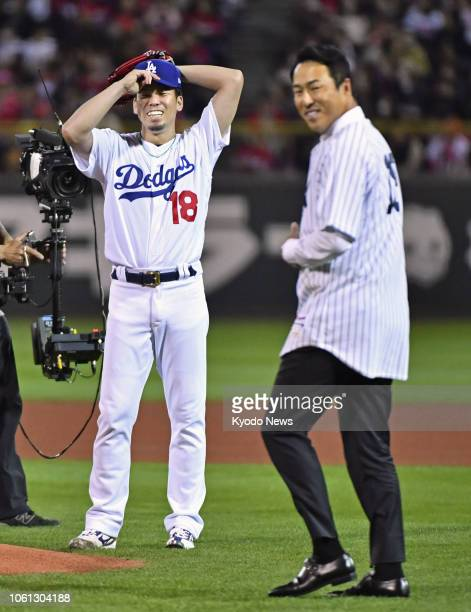 Los Angeles Dodgers pitcher Kenta Maeda greets former New York Yankees pitcher Hiroki Kuroda who threw out the ceremonial first pitch before Game 4...