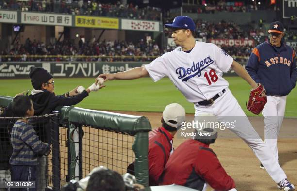 Los Angeles Dodgers pitcher Kenta Maeda hands a ball to a fan ahead of Game 4 of the MLBJapan AllStar Series at Mazda Stadium in Hiroshima on Nov 13...