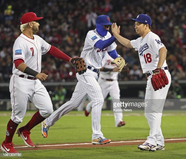 Los Angeles Dodgers pitcher Kenta Maeda highfives teammates after ending the first inning in Game 4 of the MLBJapan AllStar series at Mazda Stadium...