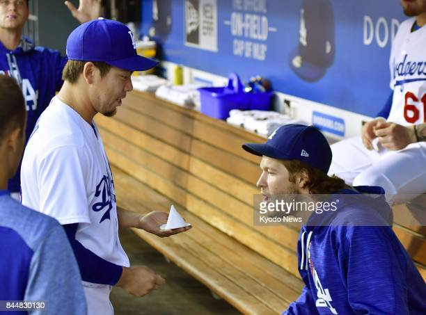 Los Angeles Dodgers pitcher Kenta Maeda shows a cone of salt an item traditionally used in his home country of Japan to ward off bad luck to teammate...