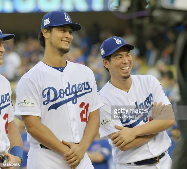 Los Angeles Dodgers pitchers Yu Darvish and Kenta Maeda lighten up during a ceremony ahead of a National League Championship Series game against the...