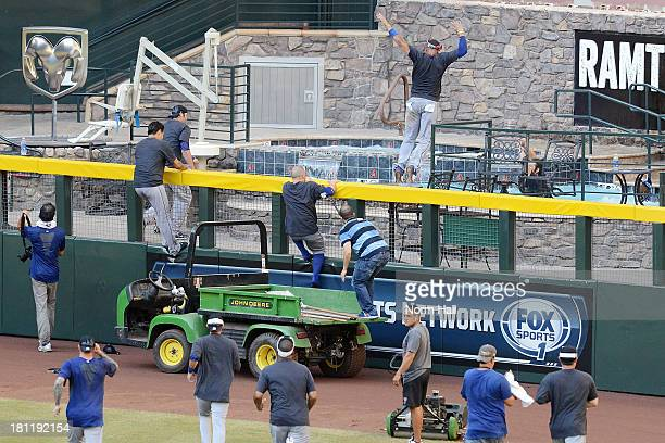 Los Angeles Dodgers players climb the right field fence and jump in the pool after clinching the National League West after a 76 win against the...