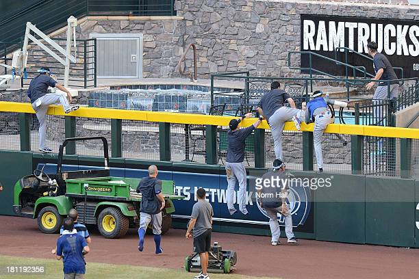 Los Angeles Dodgers players climb the right field fence and jump in the pool after clinching the National League West after a 7-6 win against the...