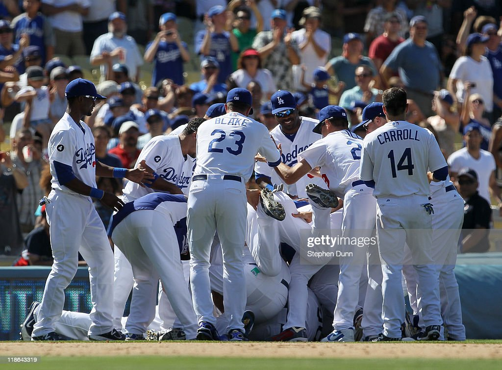 Los Angeles Dodgers players mob Dioner Navarro #30 after his walk off RBI single with two outs in the ninth inning beat the San Diego Padres on July 9, 2011 at Dodger Stadium in Los Angeles, California. The Dodgers won 1-0.
