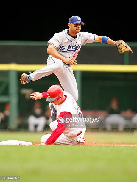 Los Angeles Dodgers' second baseman Alex Cora throws to first base to complete the double play jumping over the Cincinnati Reds' Tim Hummel in the...