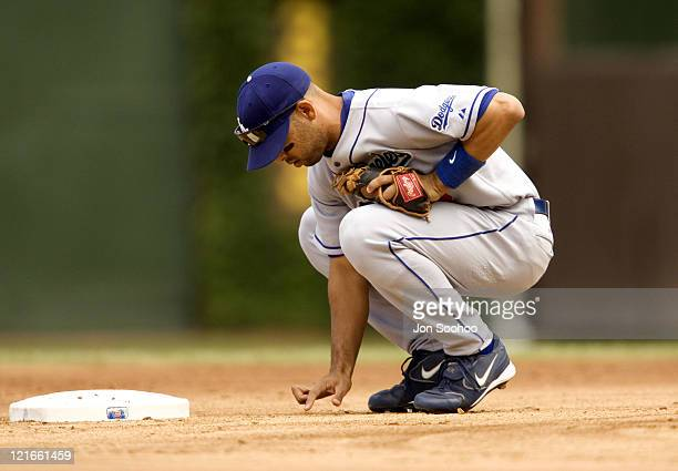 Los Angeles Dodgers second baseman Alex Cora writes on the infield dirt prior to game with the Chicago Cubs August 13 2004 at Wrigley Field in...