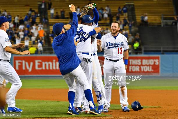Los Angeles Dodgers second baseman Brian Dozier is hugged by Los Angeles Dodgers outfielder Matt Kemp as Los Angeles Dodgers infielder Max Muncy...