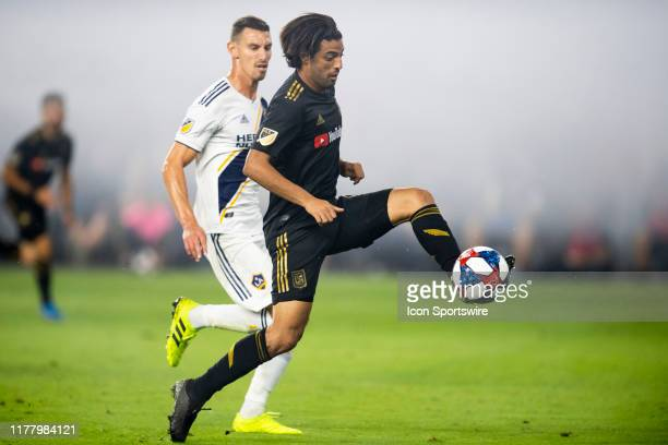 Los Angeles FC forward Carlos Vela front controls the ball infant of Los Angeles Galaxy defender Daniel Steres during a MLS Western Conference...