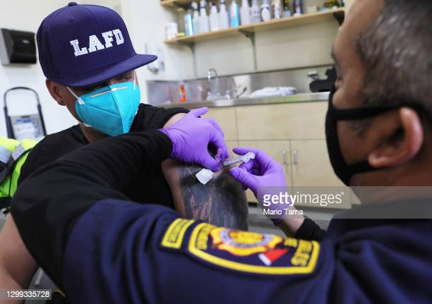 Los Angeles Fire Department firefighter receives a COVID-19 vaccination dose from firefighter paramedic Alexander Gorme at a fire station on January...