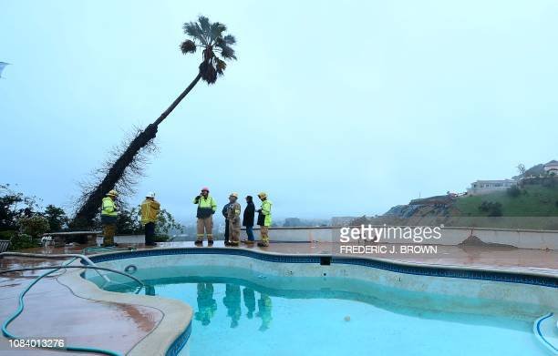 TOPSHOT Los Angeles Fire Department officers stand near a site where mud flow from another home under construction pushed out the foundation of a...