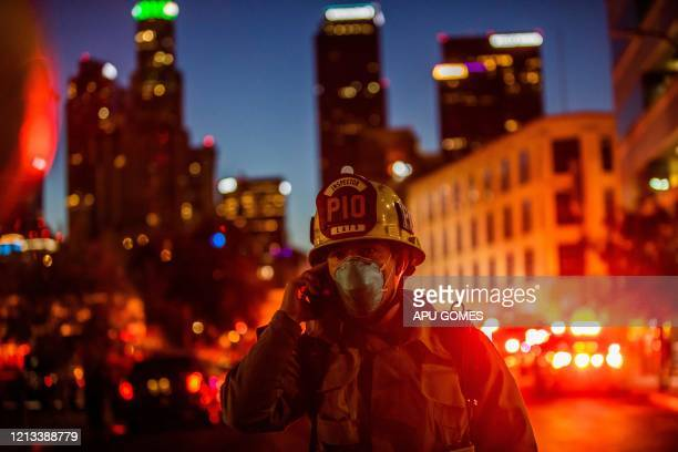 A Los Angeles Fire Department Public Information Officer wearing a facemask speaks on the phone after a fire in a singlestory commercial building...