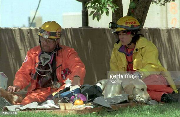 Los Angeles Firefighters Greg Gonzalez and Tracie Gallagher rest with their dogs 24 April at the site of the 19 April bomb attack on the Oklahoma...