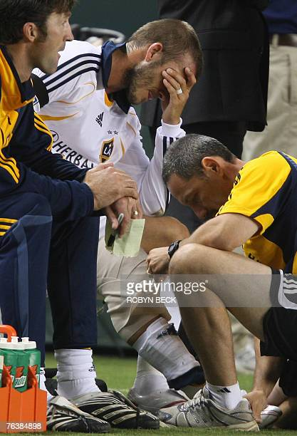Los Angeles Galaxy captain David Beckham hold his head as a trainer wraps his right knee after an injury caused by a collision with a CF Pachuca...