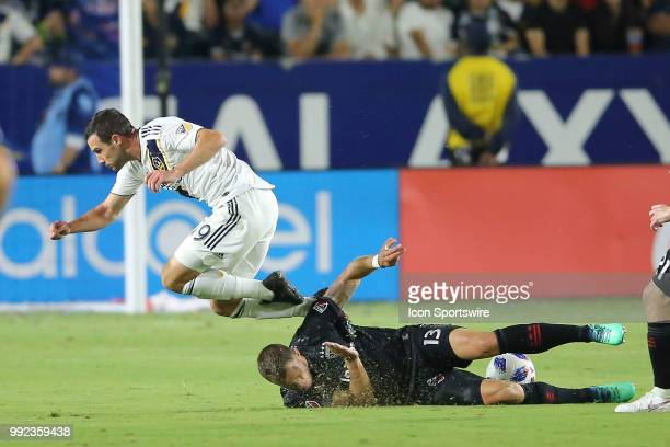 Los Angeles Galaxy forward Chris Pontius goes flying after being stripped of the ball with a sliding tackle by D.C. United defender Frederic Brillant...