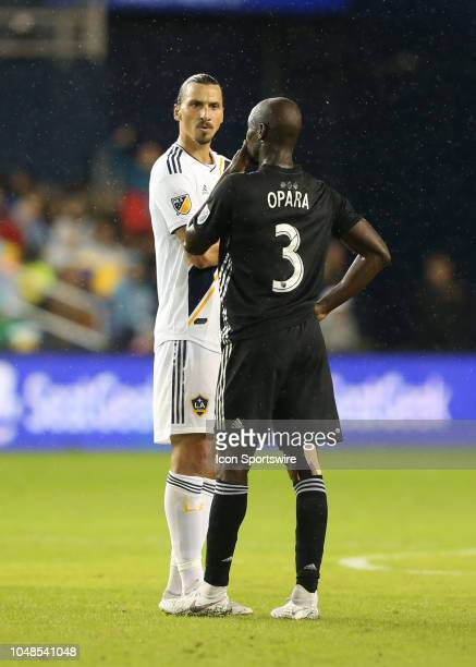 Los Angeles Galaxy forward Zlatan Ibrahimovic and Sporting Kansas City defender Ike Opara talk to each other during a break in the action during an...
