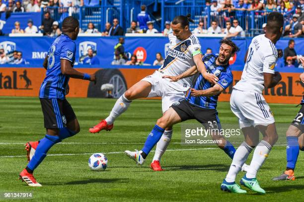 Los Angeles Galaxy forward Zlatan Ibrahimovic battles with Montreal Impact midfielder Marco Donadel to maintain control of the ball during the LA...