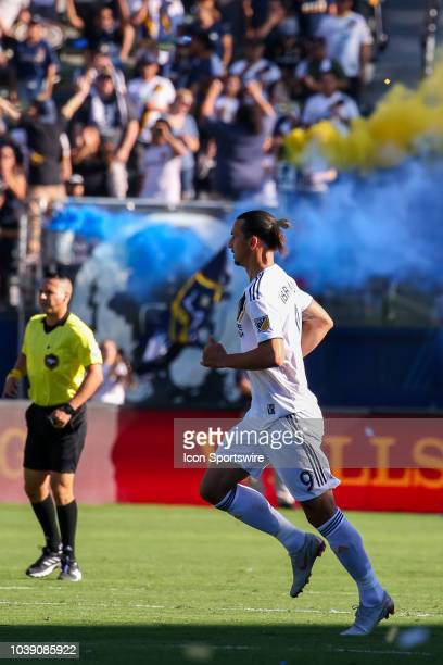 Los Angeles Galaxy forward Zlatan Ibrahimovic looks on as the Los Angeles Galaxy fans light off colorful smoke grenades in the background during a...