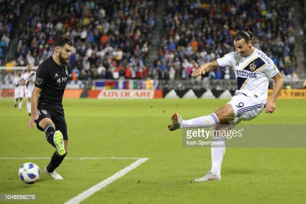 Los Angeles Galaxy forward Zlatan Ibrahimovic shoots past Sporting Kansas City midfielder Graham Zusi in the first half of an MLS match between the...