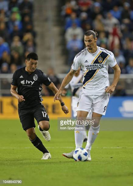 Los Angeles Galaxy forward Zlatan Ibrahimovic towers over Sporting Kansas City midfielder Roger Espinoza whiles dribbling the ball in the first half...