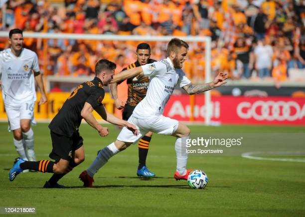 Los Angeles Galaxy midfielder Aleksandar Katai dribbles the ball with Houston Dynamo defender Adam Lundqvist in pursuit during the MLS match between...