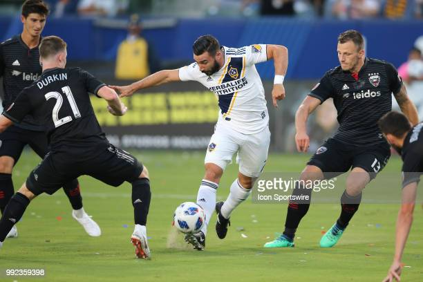 Los Angeles Galaxy midfielder Romain Alessandrini gets off a near perfect pass between defenders in DC United defender Frederic Brillant DC United...