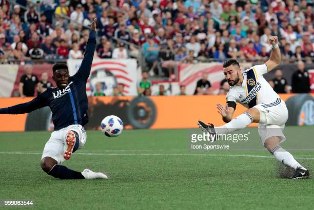 Los Angeles Galaxy midfielder Romain Alessandrini shoots as New England Revolution defender Jalil Anibaba tries to block it during a match between...