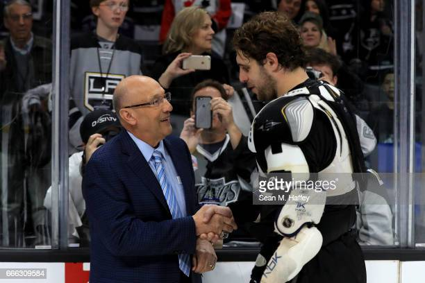 Los Angeles Kings broadcaster Bob Miller shakes hands with Anze Kopitar of the Los Angeles Kings after a game against the Chicago Blackhawks at...