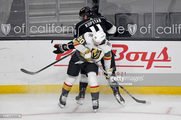 Los Angeles Kings Center Anze Kopitar knocks the puck out of the air with his glove while battling with Vegas Golden Knights Center Chandler...