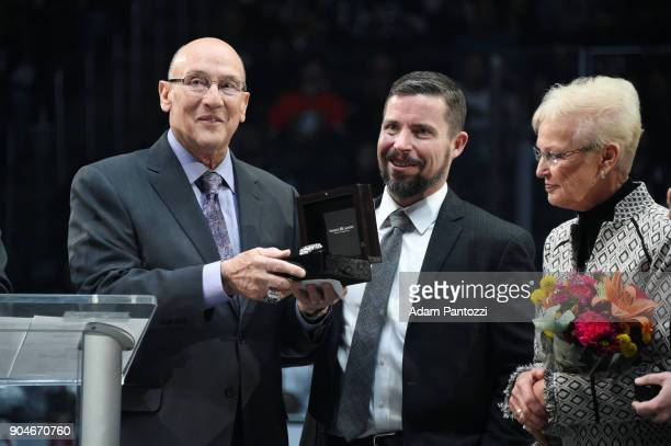 Los Angeles Kings Chief Operating Officer Kelly Cheeseman presents former broadcaster Bob Miller with a watch during his bannerraising ceremony...