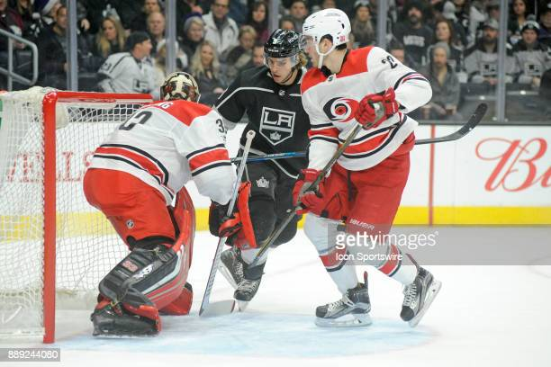 Los Angeles Kings forward Adrian Kempe battles with Hurricanes forward Sebastian Aho as goaltender Scott Durling looks on during the first period of...