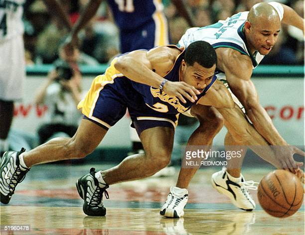 Los Angeles Laker Derek Fisher battles Charlotte Hornet David Wesley for control of a loose ball in the first half at the Charlotte Coliseum on 16...