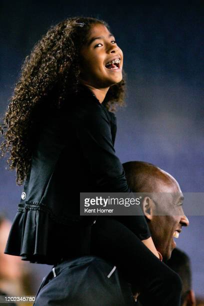 Los Angeles Laker Kobe Bryant stands on the sideline with his daughter Gianna MariaOnore Bryant on his shoulders prior to the start of the game...