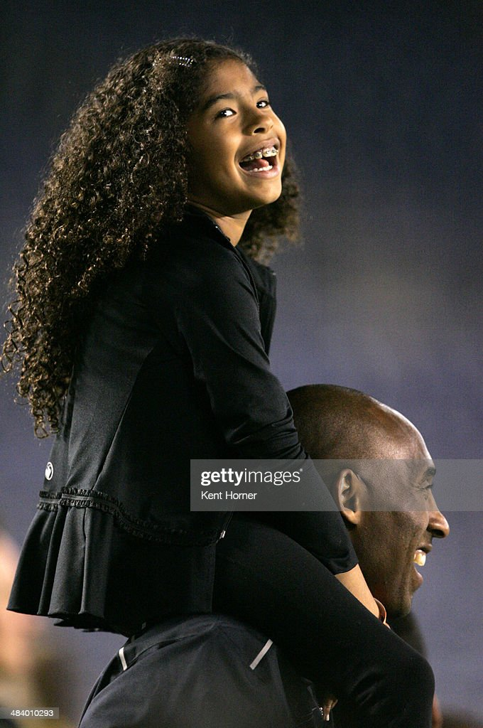 Los Angeles Laker Kobe Bryant stands on the sideline with his daughter Gianna Maria-Onore Bryant on his shoulders prior to the start of the game against the United States and China during an international firendly match at Qualcomm Stadium on April 10, 2014 in San Diego, California.