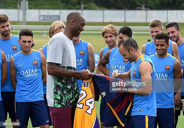 Los Angeles Lakers basketball star Kobe Bryant watches as Barcelona team captain Andrés Iniesta Luján signs a jersey watched by other members of the...