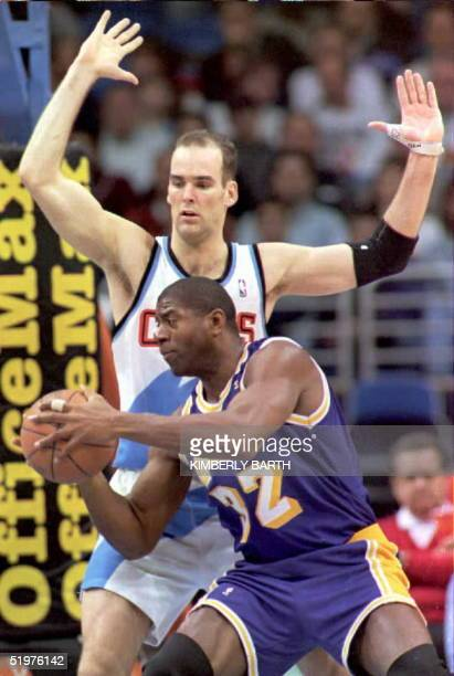 Los Angeles Lakers' Earvin 'Magic' Johnson makes a move toward the basket despite pressure from Cleveland Cavaliers' forward Danny Ferry in game...