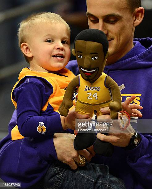 Los Angeles Lakers fan William Boatright, 21 months, plays with his Kobe Bryant doll as his father, Joshua Boatright, holds him prior to the Lakers...