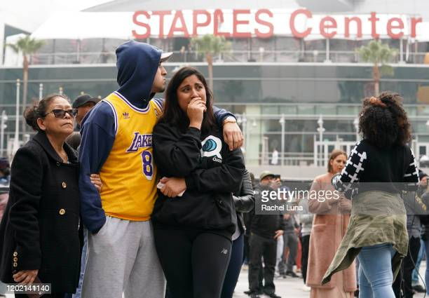 Los Angeles Lakers fans Lilian Gamez Gabriel Gamez and Angelica Rodriguez mourn the death of retired NBA star Kobe Bryant outside the Staples Center...