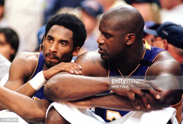 Los Angeles Lakers forward Kobe Bryant speaks with teammate Shaquille O'Neal as they sit out the end of the fourth quarter against the Phoenix Suns...