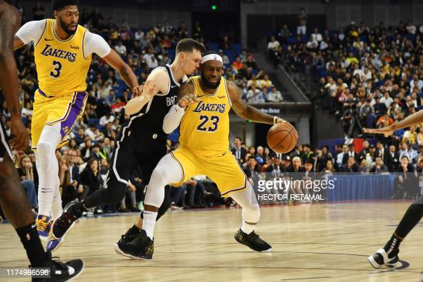 TOPSHOT Los Angeles Lakers forward LeBron James is guarded by Rodions Kurucs of the Brooklyn Nets during their National Basketball Association...