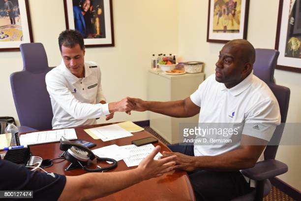 Los Angeles Lakers General Manager Rob Pelinka and President of Basketball Operations Magic Johnson shake hands in the draft room during the 2017 NBA...