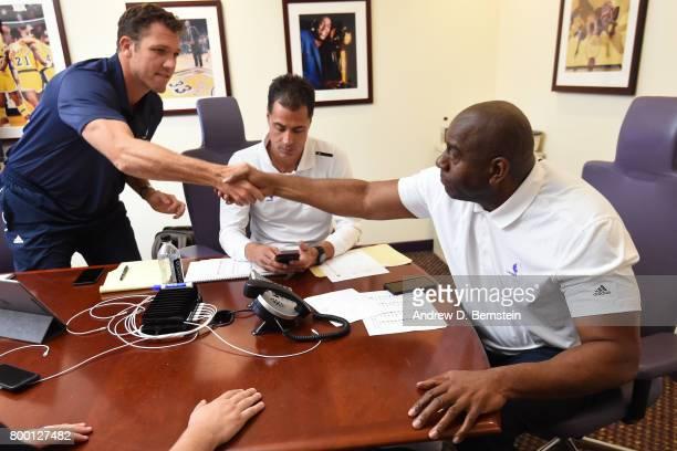 Los Angeles Lakers General Manager Rob Pelinka Head Coach Luke Walton and President of Basketball Operations Magic Johnson shake hands and make a...