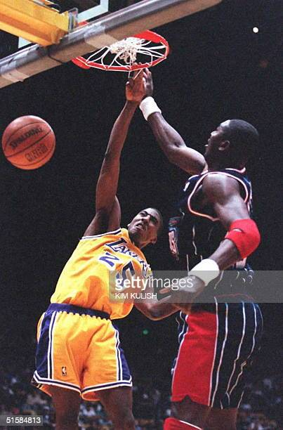 Los Angeles Lakers guard Eddie Jones slams in a shot past Houston Rockets Hakeem Olajuwon during first half action 3 March at the Great Western Forum...