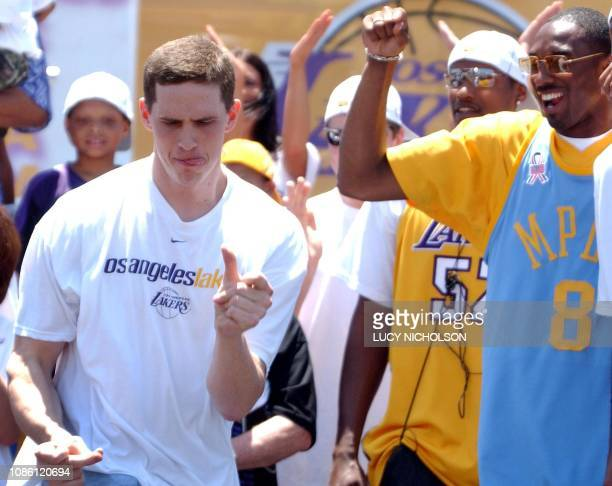 Los Angeles Lakers' guard Kobe Bryant cheers as teammate Mark Madsen dances on stage in celebration of the team's third consecutive NBA championship...