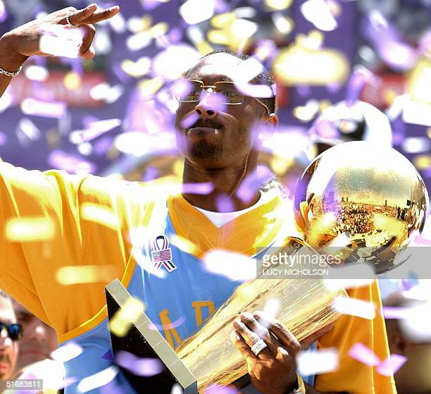 Los Angeles Lakers' guard Kobe Bryant lifts up the championship trophy in celebration of the team's third consecutive NBA championship at the Staples...