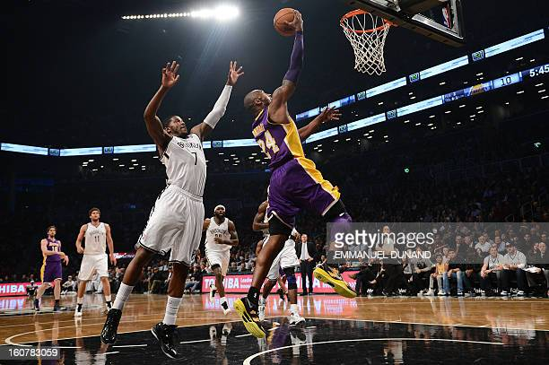 Los Angeles Lakers' Kobe Bryant drives the ball past Brooklyn Nets Joe Johnson during their NBA game at the Barclays Center in the Brooklyn borough...