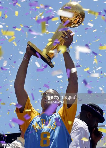 Los Angeles Lakers' Kobe Bryant lifts the championship trophy during the Lakers' celebration of their third consecutive NBA championship 14 June 2002...