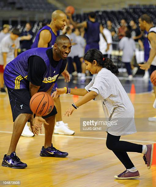 Los Angeles Lakers' Kobe Bryant plays with a child during a basketball clinic held after a training session on October 6 2010 at Palau Sant Jordi in...